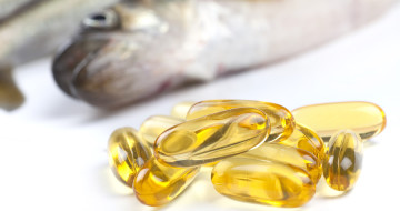 Close up of a cod liver fish oil capsule a nutritional supplement high in omega-3 fatty acids EPA DHA and high levels of vitamin A and vitamin D. Fresh fish are in the background.